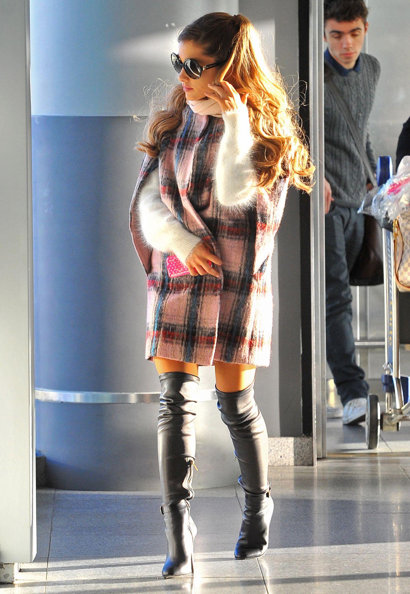 Das rosafarbene Schottenmuster-Cape kombiniert Ariana Grande mit einem kuscheligen Cashmere-Pullover.