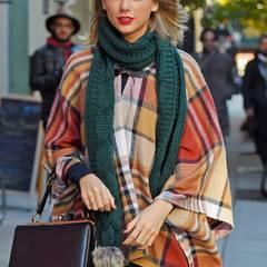 Taylor Swift hat ein Auge für tolle Farbkombinationen. Das karierte Cape mit grünem Schal ist das perfekte Outfit für einen Herbstspaziergang.