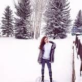 Mit Rollkragenpullover und Winterjacke genießt Liliana den frisch gefallenen Schnee.