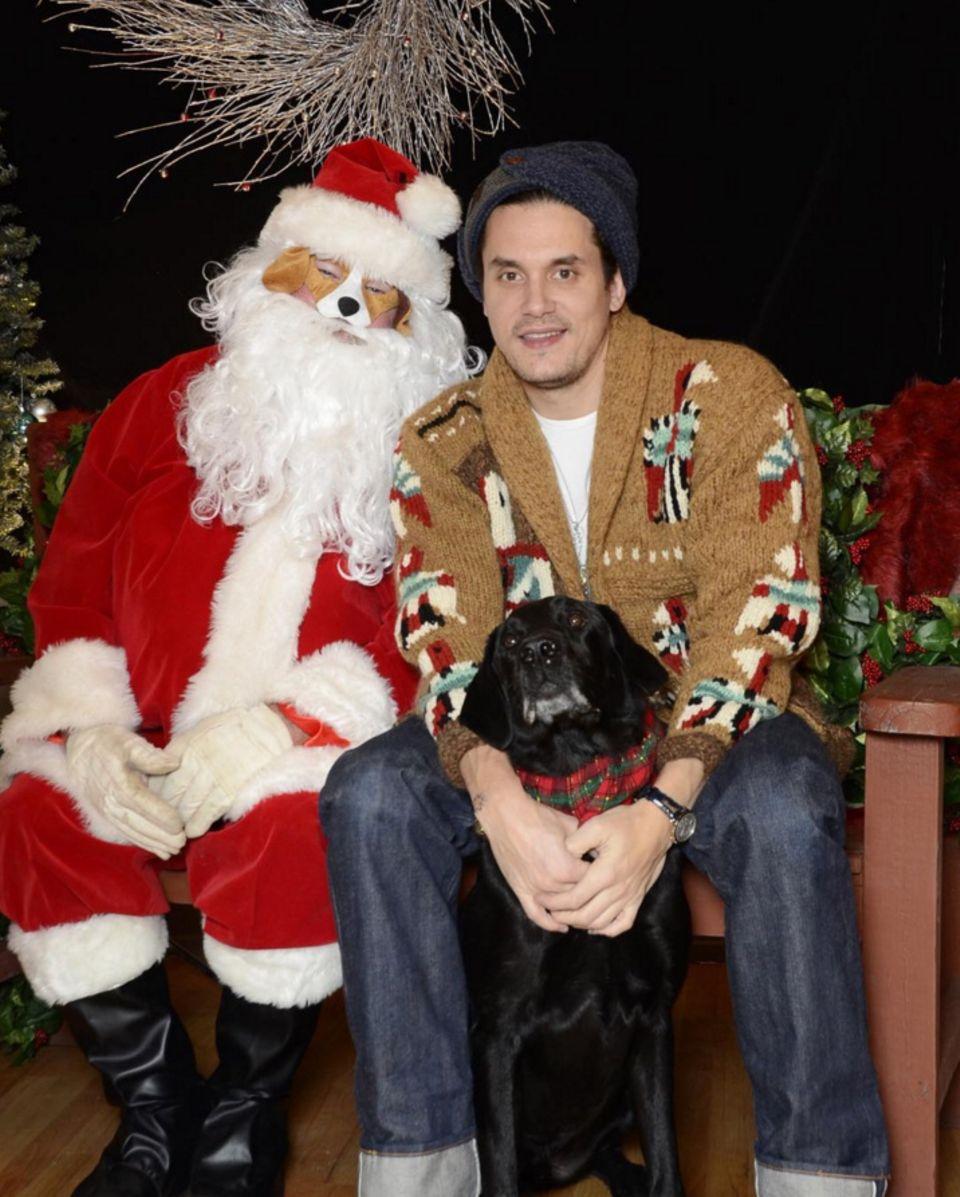 John Mayer ist in Weihnachtsstimmung! Er sitz bei einem schrägen Weihnachtsmann mit Hundegesicht und seinem täglichen Begleiter Moose in einem kuscheligen Cardigan.