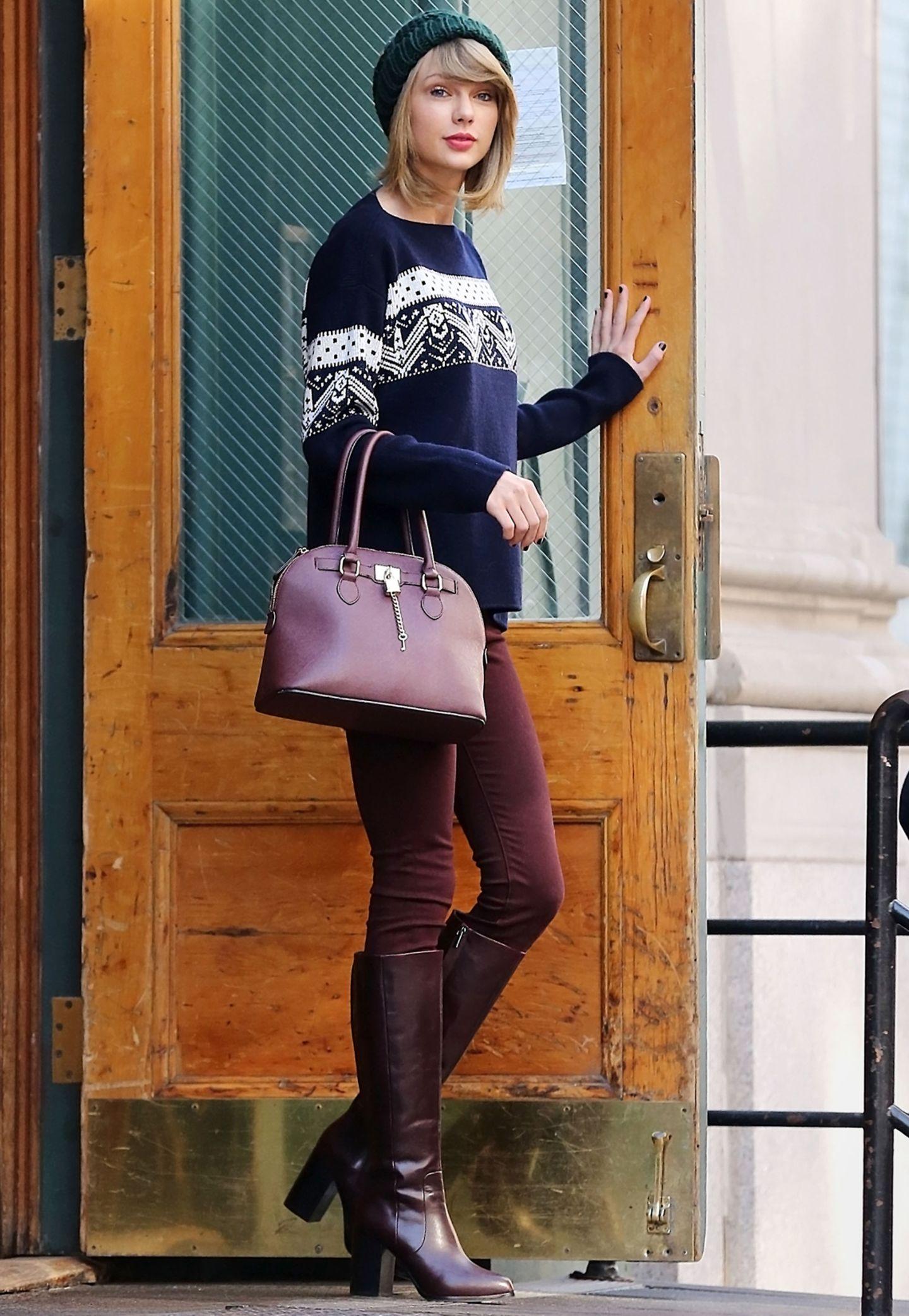 Taylor Swift erzielt einen modisch weihnachtlichen Alltags-Look, indem sie zu einem Sweater mit klassischem Norweger-Muster eine Skinny Jeans sowie elegante Stiefel und Handtasche in der Trend-Farbe Burgunder wählt.