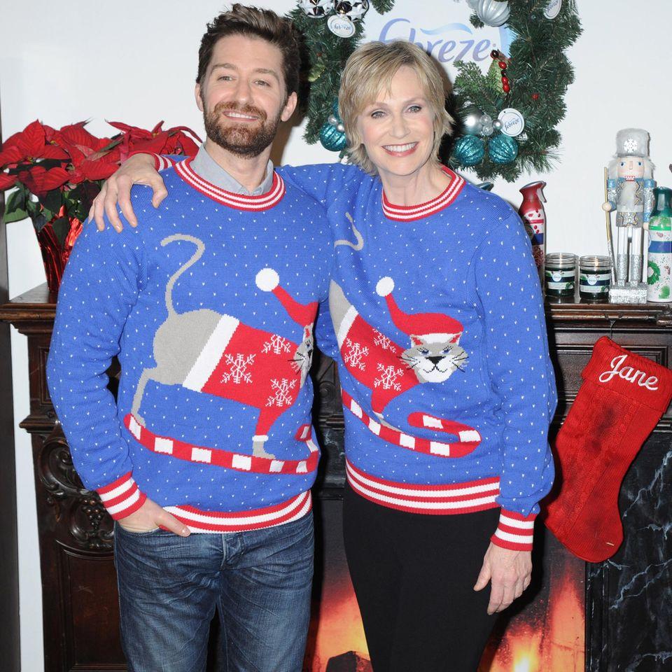 In weihnachtlichen Katzenpullovern posieren Matthew Morrison und Jane Lynch vor den Kameras.