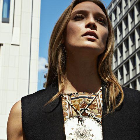 Ärmelloses Kleid aus persisch gemustertem Wollmousseline, von Hermès. Schwarze Kaschmirweste von Dior. Amulettkette und Oberarmschmuck sind Leihgaben der Tribal Art Galerie Dogon, Berlin.