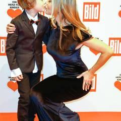 Schauspielerin Xenia Seeberg drückt ihrem Sohn einen Kuss auf.