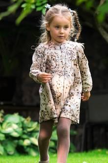 Sole Trussardi trägt ein gemustertes beiges Kleid, dazu eine passende Strumpfhose und süße Schühchen. Von oben bis unten ist der gesamte Look aufeinander abgestimmt.
