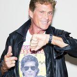 """K.I.T.T. bitte kommen: Erneut stellt David Hasselhoff mit einem """"Party Your Hasselhoff""""-Shirt seinen Humor unter Beweis. Mit derber Lederjacke und dem auffälligen Gürtel sieht der Schauspieler fast aus wie in seinen besten """"Knight Rider""""-Zeiten."""