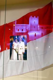 Der feierlich erleuchtete Palast reflektiert in einem Schaufenster, in dem zu Ehren der Thronfolger-Geburt ein Foto von Fürstin Charlène und Fürst Albert hängt.