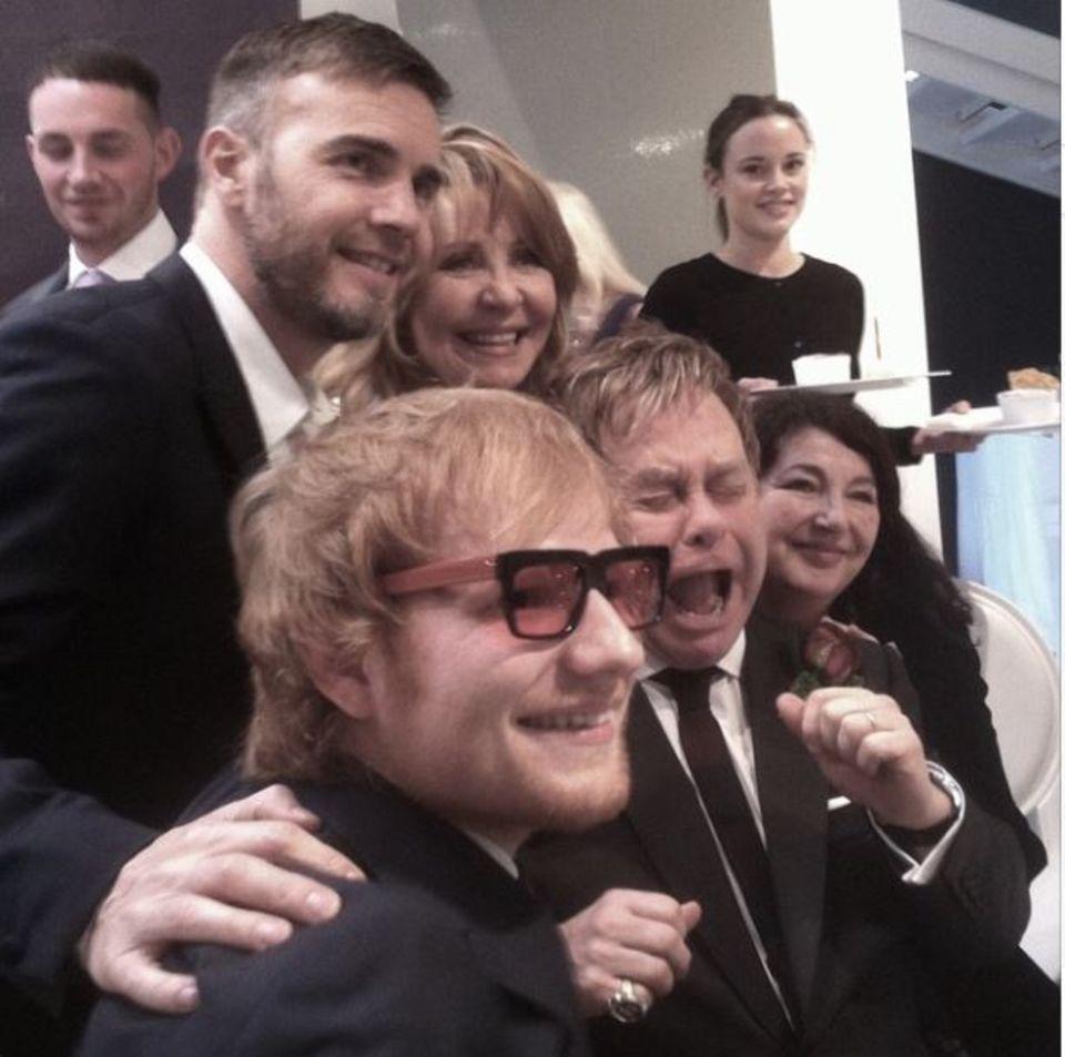 Elton John die Brille klauen? Das traut sich nur Ed Sheeran. Auf dem Gruppenfoto zieht der Bräutigam eine Schnute, Sheeran scheint's zu freuen und Gary Barlow setzt im Hintergrund das schillernde Popstar-Lächeln auf.