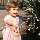 1979  Prinz Carl Philip, der im Mai geboren wurde, hat unter dem Weihnachtsbaum im Stockholmer Schloss einen Frosch entdeckt. Seine große Schwester Victoria scheint auch etwas Interessantes bekommen zu haben, was sie gerne zeigen möchte.
