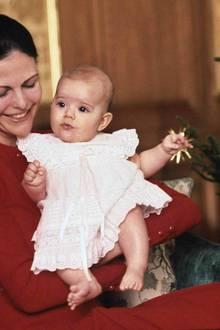 1977  Prinzessin Victoria ist knapp fünf Monate alt, als sie zum ersten Mal Weihnachten erlebt. Im weißen Kleidchen und bei ihrer Mutter Silvia auf dem Arm guckt sie ganz erstaunt, als das erste Weihnachtsbild von ihr entsteht.
