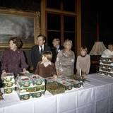 1978  Königin Juliana verteilt gemeinsam mit ihrer Tochter, der späteren Königin Beatrix und deren Kindern Weihnachtsgeschenke. Prinzgemahl Bernhard (im Hintergrund) ist ebenso dabei wie Prinz Johan Friso und Prinz Willem-Alexander, der später seiner Mutter und Großmutter als König auf den Thron folgen wird.