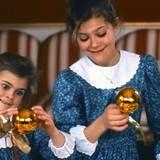 1988  Prinzessin Madeleine und Prinzessin Victoria steht der Sinn beim weihnachtlichen Fototermin mit den glänzenden Christbaumkugeln wohl nicht nach einem prinzessinnenhaften Lächeln. Sie schneiden lieber Grimassen.