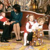 1982  Prinzessin Madeleine, die im Juni geboren wurde, feiert das erste Weihnachtsfest. Ihre beiden älteren Geschwister Victoria und Carl Philip sind ebenso weihnachtlich angezogen wie die Kleine, spielen aber schon auf einem Schaukelpferd.