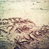 """""""Frohes neues Jahr! Die Kutchers"""": Mit diesen Worten, die Ashton Kutcher in den Sand geschrieben hat, heizt er die Spekulationen an, dass er und Mila Kunis bereits verheiratet sein könnten."""