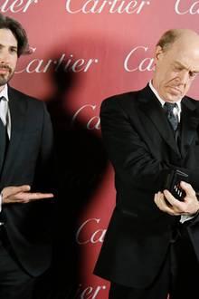 """J.K. Simmons bekommt von Jason Reitman den """"Spotlight Award"""" überreicht, weiß aber offenbar nicht so richtig, wo bei der Statuette oben und unten ist."""