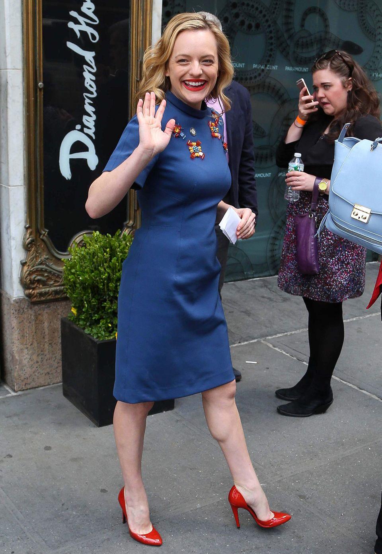 """Eine gehörige Portion """"Mad Men"""" steckt in diesem eleganten Outfit von Schauspielerin Elisabeth Moss. Ein willkommener Farbtupfer sind die roten Lacklederschuhe zum bestickten, blauen Etuikleid."""