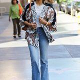 Jessica Alba kombiniert ihr Jeans- und T-Shirt-Outfit mit einer Kimono-ähnlichen Bluse mit Ethno-Muster.