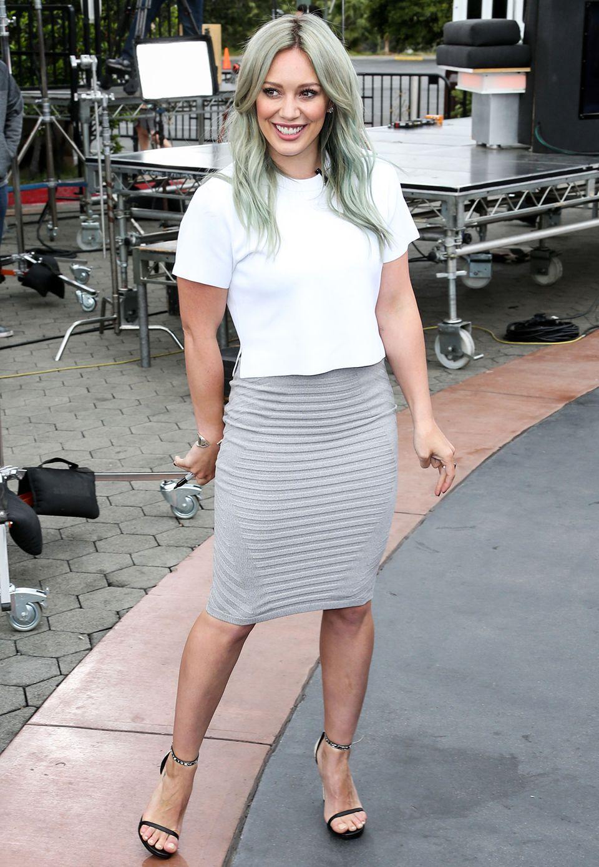 Als hätte sie ihren Look auf die grau gefärbten Haare abgestimmt trägt Hilary Duff ein weißes, kastiges Shirt zum hellgrauen Stretchrock.