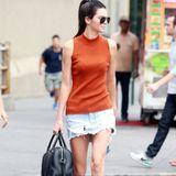 """Kendall Jenner flaniert in einem orangefarbenen Top und Denim-Rock im Used-Look durch New York. Eine schwarze """"Givenchy""""-Handtasche und hellbraune Wildleder-Booties runden ihr Outfit ab."""