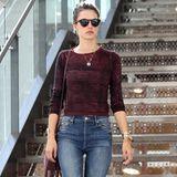 Alessandra Ambrosio trägt ein Modell der super angesagten, verkürzten Flared Jeans mit hohem Bund und kombiniert dazu Schlangenleder-Loafers und ein gestreiftes Sweatshirt.