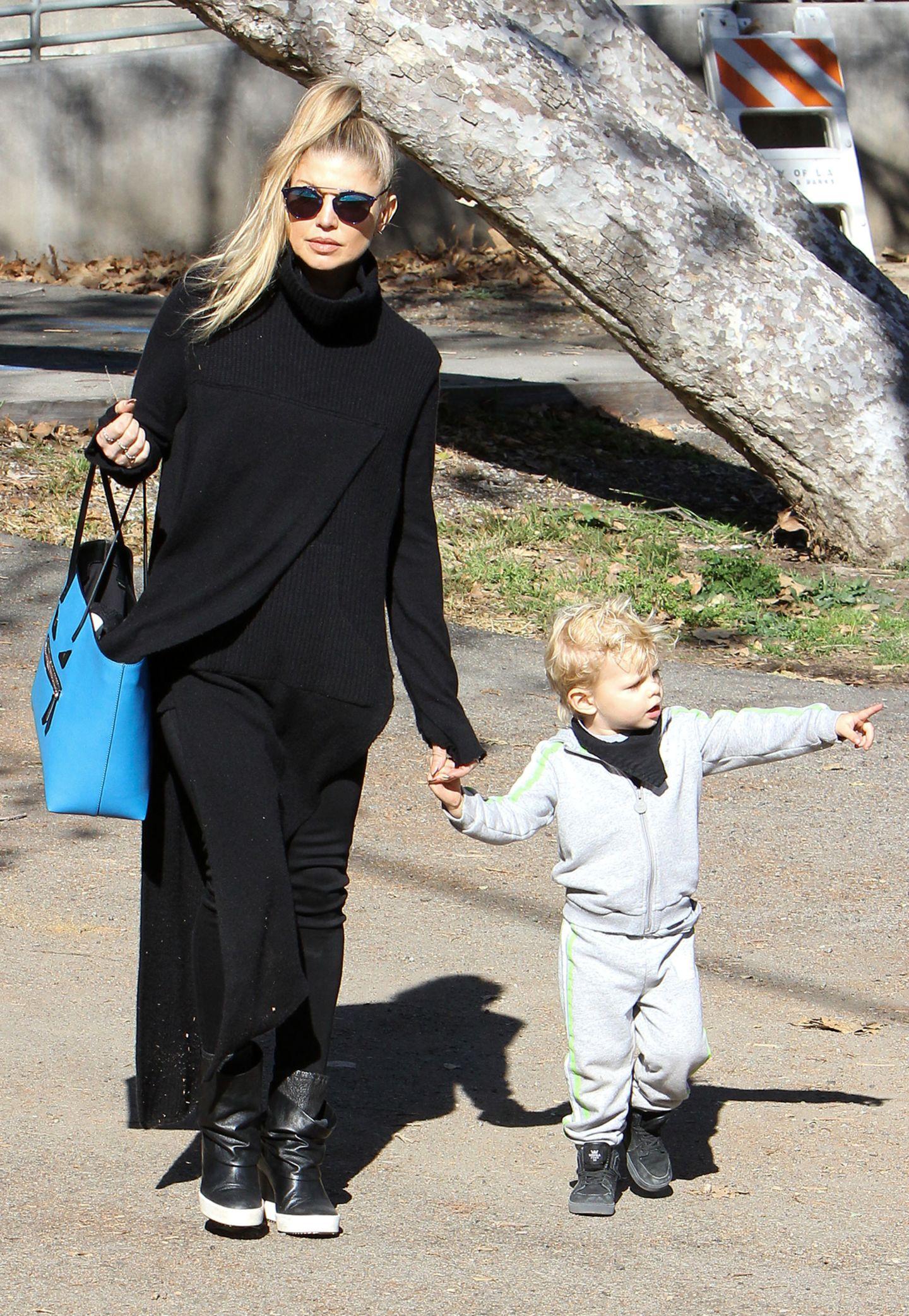 Fergie ist nicht nur eine super lässige Mama, sondern noch dazu eine wahnsinnig modische. Der komplett schwarze Kuschel-Looks wird durch den blauen Shopper erfolgreich aufgepeppt.