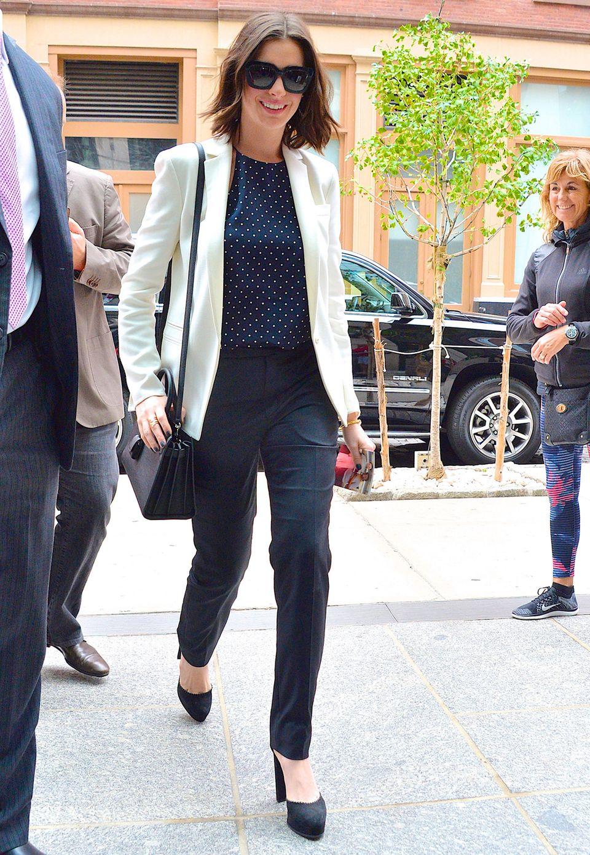 10 Punkte für diesen tollen Look! Anne Hathaway kombiniert eine navyblaue Pünktchenbluse von Zimmermann zu schmal geschnittenen Stoffhosen und einem cremeweißen Blazer mit Revers von Akris. Die kleine Henkeltasche mit Schulterriemen stammt von Saint Laurent.