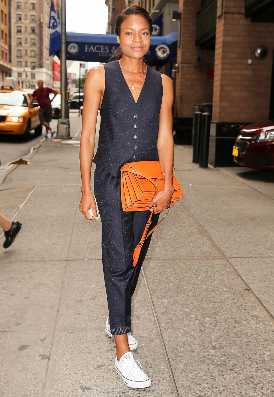So stylt man Hose und Weste weiblich und super schick: Naomie Harris kombiniert zum blau-gepunkteten Ensemble eine knallorangene Schultertasche und weiße Chucks von Converse.