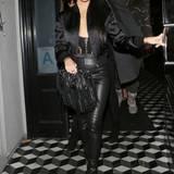 Kourtney Kardashian unterstreicht ihre Kurven, indem sie ein tiefes Dekolleté zur hautengen Lederhose kombiniert. Ihr Satin-Blouson und die Fransen-Tasche runden den sexy Material-Mix ab.