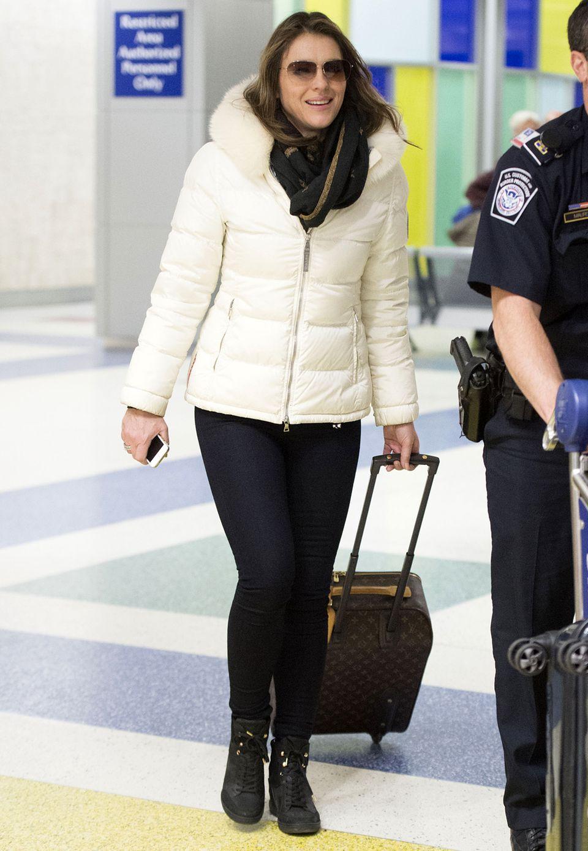 Von wegen Winterfrust! Liz Hurley trotzt den kalten Temperaturen und reist in einer kuscheligen, cremeweißen Daunenjacke mit Pelzkragen. Dazu kombiniert sie Skinny-Jeans und bequeme High-Top-Sneakers.