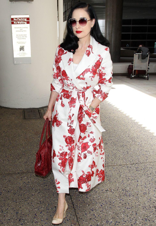 Was für eine Erscheinung! Burlesque-Künstlerin Dita von Teese reist top gestylt in einem weiß-roten Mantel mit Taillengürtel und Rosendruck.