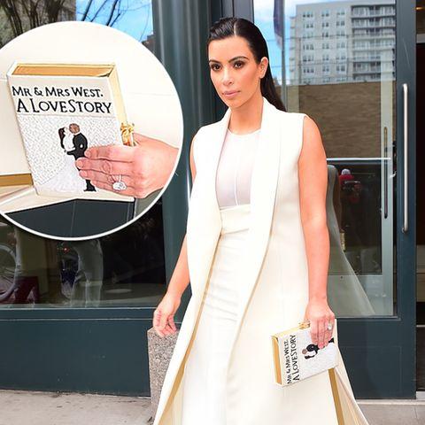 """Im cremeweißen Outfit mit Marlene-Hose und langer Weste macht Kim Kardashian auf den ersten Blick einen tollen Eindruck. Beim genaueren Betrachten ihrer Buch-Clutch dürfen dann aber doch wieder die Augen gerollt werden. Das Geltungsbedürfnis von Kimye und ihrer """"Lovestory"""" ist einfach nicht zu toppen."""