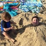 August 2015  Jason Biggs lässt sich von seinem Sprössling im Sand einbuddeln.