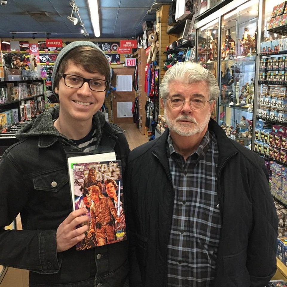 """März 2015  Welch eine Ehre! George Lucas besucht den Comicladen """"Midtown Comics"""" am Times Square in New York. Und ein sehr stolzer Fan lässt sich mit ihm ablichten, in der einen Hand ein """"Star Wars"""" Comic und ein unbezahlbares Lächeln auf den Lippen."""