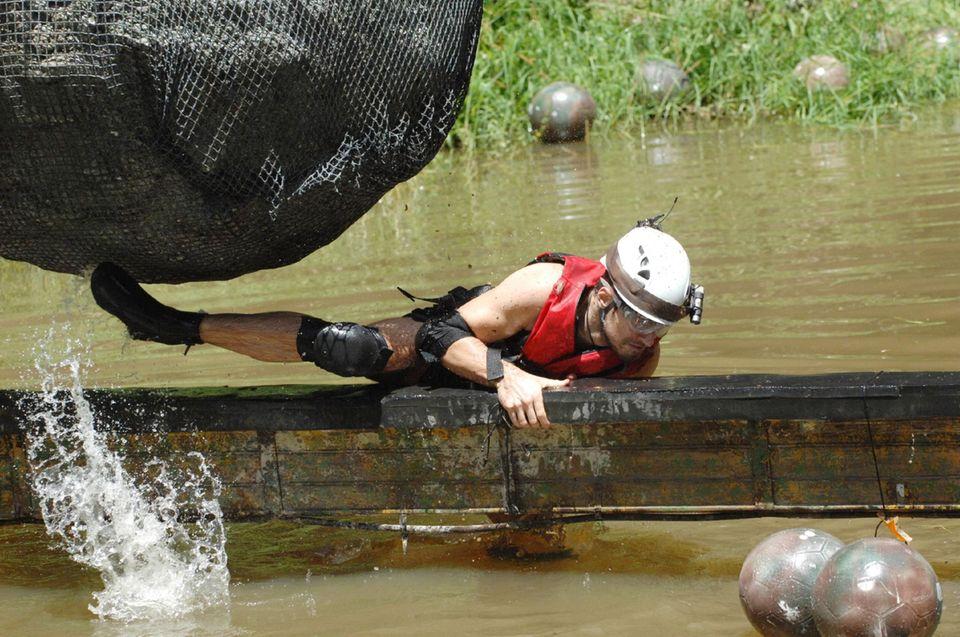 """Tag 14  Jörn Schlönvoigt muss auf einer wackeligen Planke über einen See balancieren, um an die begehrten Sterne zu kommen. Hinzu kommt, dass er einem riesigen """"Felsbrocken"""" ausweichen muss und mit Wasserstrahlen und Bällen beschossen wird."""