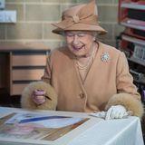 2. Februar 2015: Amüsiert schaut Queen Elizabeth auf ein Bild von sich selbst, das sie in der Feuerwehrstation von Kings's Lynn unterschreiben soll.