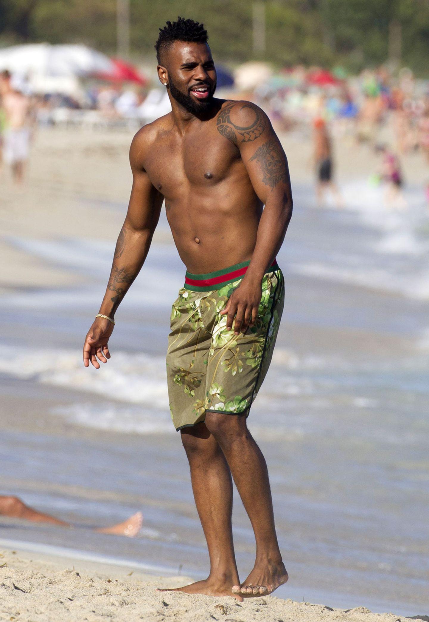 Jason Derulo präsentiert stahlhart seinen Body mit Tattoos und wählt als Kontrast einen Blütenshort in milden Grüntönen.