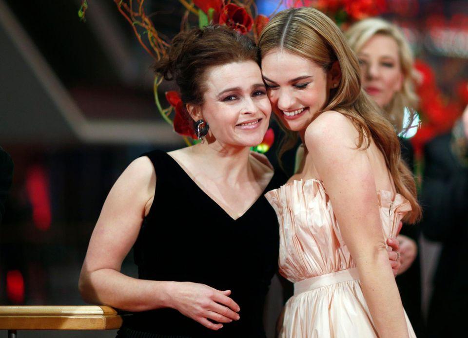 """Die """"Cinderella""""-Schauspielerinnen Helena Bonham Carter und Lily James kuschln auf dem roten Teppich."""