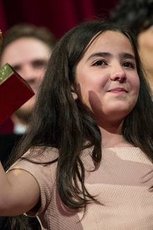 """Der Goldene Bär geht an Regisseur Jafar Panahi für seinen Film """"Taxi"""". Der iranische Regimekritiker darf das Land nicht verlassen, deshalb nimmt seine Nichte Hana Saeidi die Trophäe entgegen."""