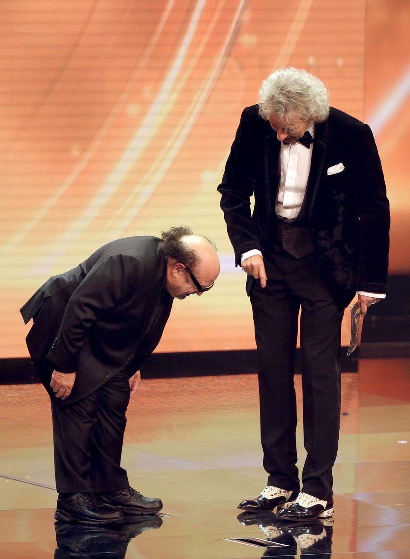 Danny DeVito inspiziert Thomas Gottschalks Schuhe.