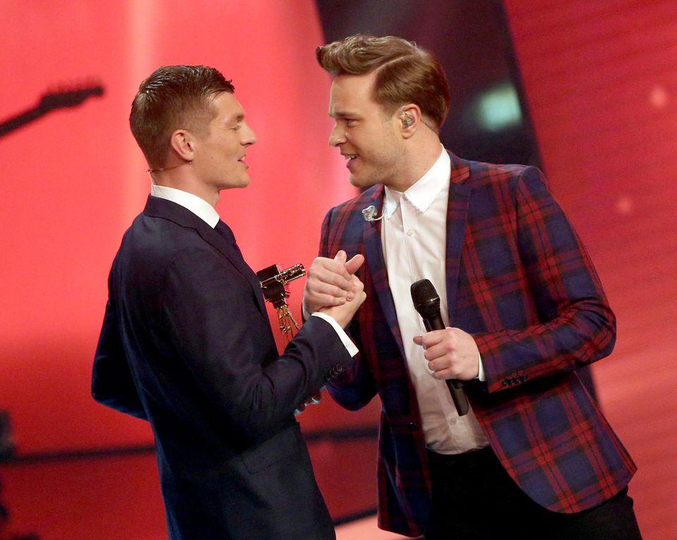Weltmeister Toni Kroos überreicht dem britischen Sänger Olly Murs die Goldene Kamera für die beste internationale Musik.