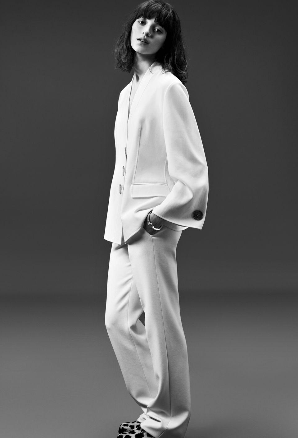 Anzüge  Hosenanzüge verlieren ihre Strenge durch weite Schnitte und weich fallende Stoffe. Zu diesem Anzug gehört ein kragenloser Cardigan mit ausgestellten Ärmeln und eine lässige Hose. Dazu Leo-Schuhe. Alles von Giorgio Armani. Armreif von Tiffany & Co.
