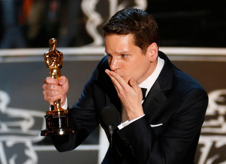 """Autor Graham Moore gewinnt für """"The Imitation Game"""" den Oscar für das """"beste adaptierte Drehbuch"""" und wirft vor Glück mit Handküssen um sich."""