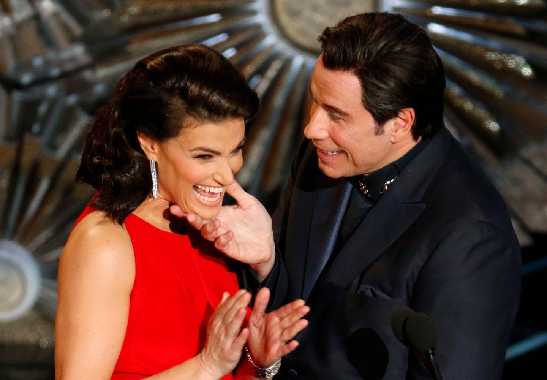 Damit es nicht wieder zu Versprechern kommt, kündigt dieses Mal Idina Menzel John Travolta an, erlaubt sich dabei jedoch einen kleinen Scherz.
