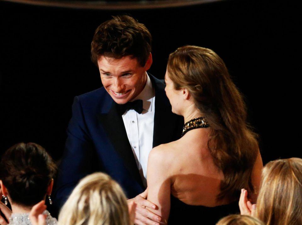 """Eddie Redmayne kann es kaum glauben, er gewinnt als """"bester Hauptdarsteller"""", seine Frau Hannah Bagshawe gratuliert."""