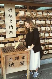 Verdauungspause: Drew Barrymore wird in Tokyo nicht nur von einzigartigen Restaurants gelockt. Auch eine Sightseeing-Tour steht bei der Schauspielerin auf dem Programm. Sie betet nach alt japanischer Tradition für ihre Töchter Olive und Frankie.