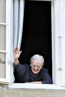 Königin Margrethe, nun offiziell 75 Jahre alt, grüßt aus einem Fenster von Schloss Fredensborg ihre royalen Gäste, die sich darunter versammelt haben.