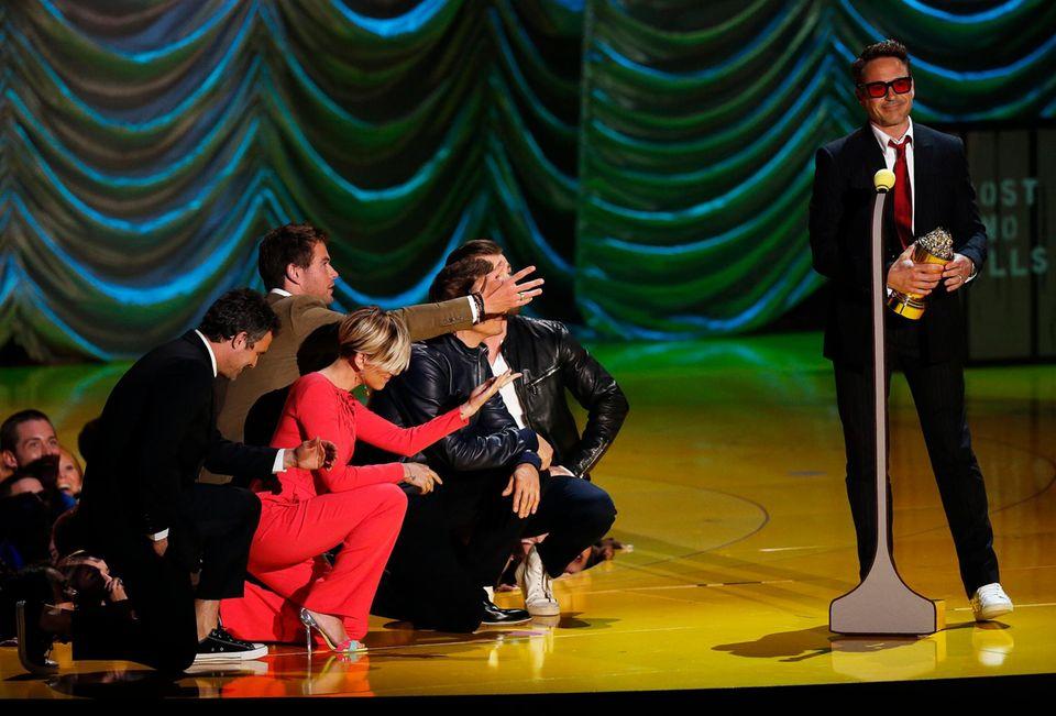 "Robert Downey Jr. nimmt den ""MTV Generation Award"" entgegen. Seine ""Avengers""-Kollegen knien vor ihm nieder."