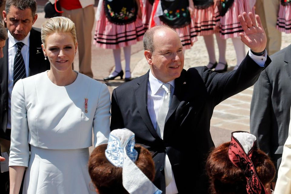 Glücklich winkt Fürst Albert den Fans, Gattin Charlène hält er fest an der Hand.