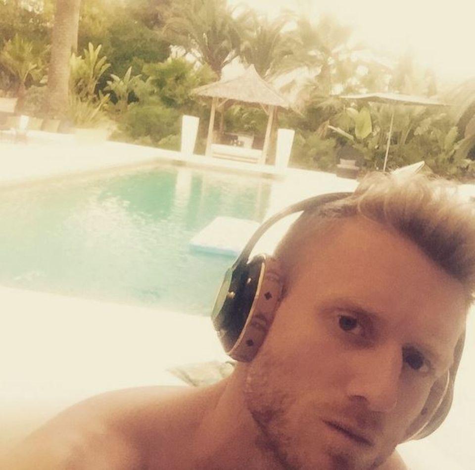 André Schürrle entspannt sich nach dem Pokalgewinn mit dem VfL Wolfsburg bei Musik und Sonne am Pool.