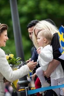 Königin Silvia nimmt sich die Zeit, einem kleinen Mädchen die Hand zu schütteln. Gemeinsam mit König Carl Gustaf (ganz links) ist sie zu den Nationaltagsfeierlichkeiten in Örebro.